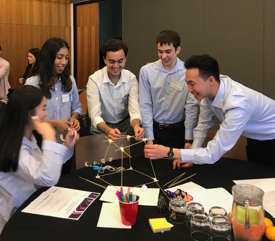 Participants building a tower with spaghetti